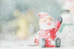 在降雪背景的一陶瓷圣诞老人圣诞快乐文本 可爱的圣诞快乐和新年快乐2018年在降雪 免版税库存照片