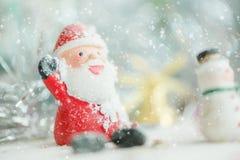 在降雪背景的一陶瓷圣诞老人圣诞快乐文本 可爱的圣诞快乐和新年快乐2018年在降雪 库存图片