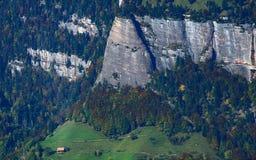 在陡峭的山墙壁下的农舍 库存图片