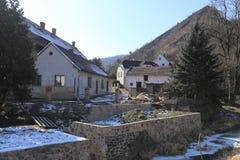 在陡峭的岩石下的老村庄房子 免版税库存照片
