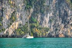 在陡峭的岩石岸的背景的海洋筏 免版税库存图片