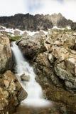 在陡峭的崎岖的峰顶下的岩石瀑布 库存图片