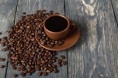 在陶瓷杯,咖啡豆的咖啡在木桌上驱散了近, 库存照片