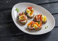 在陶瓷板材的蕃茄和乳酪bruschetta在黑暗的木背景 健康早餐,快餐 库存照片