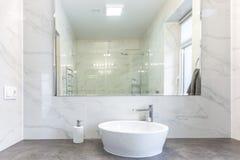在陶瓷水龙头水槽附近的肥皂和香波分配器与龙头在昂贵的顶楼卫生间里 免版税图库摄影