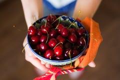 在陶瓷碗和毛巾的樱桃在手上 免版税库存图片