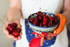 在陶瓷碗和毛巾的樱桃在手上 库存图片