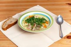 在陶瓷碗的鸡汤有面包片的,匙子 免版税库存照片