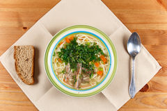 在陶瓷碗的鸡汤有面包片的,匙子 免版税库存图片