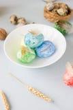 在陶瓷碗,明亮和通风射击的绿色,黄色和蓝色复活节彩蛋 免版税库存照片