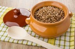 在陶瓷罐,盒盖,在餐巾的木匙子的准备的荞麦 免版税图库摄影