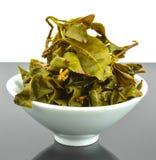 在陶瓷茶杯的酿造的充分的叶子绿茶 库存照片