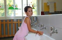 在陶瓷水槽的小女孩洗涤的手在卫生间o里 免版税库存照片