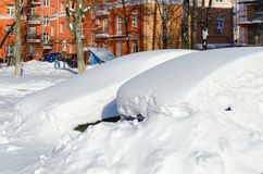 在随风飘飞的雪下的停放的汽车在降雪以后的城市围场在3月 免版税库存照片