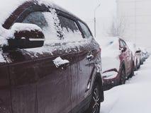 在随风飘飞的雪下的汽车 库存照片