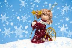 在随风飘飞的雪的天使玩偶与雪花 免版税图库摄影