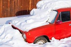 在随风飘飞的雪的老红色汽车 免版税库存照片