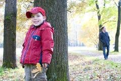在隐藏他的结构树的男孩爸爸之后 免版税库存图片