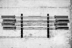 在难看的东西墙壁上拧紧的立场的四个杠铃重量酒吧为在健身房的黑色的建身的举重体育做准备 库存照片