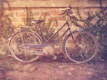 在难看的东西墙壁房子的老葡萄酒自行车停车处有减速火箭的filt的 免版税库存图片