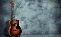 在难看的东西墙壁背景的吉他 免版税库存图片
