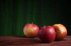 在难看的东西木头和橙色背景的红色苹果 免版税图库摄影