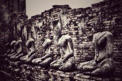 在难看的东西砖墙背景的老打破的菩萨雕象与vi 免版税图库摄影