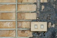 在难看的东西肮脏的墙壁上的电开关。 免版税库存照片
