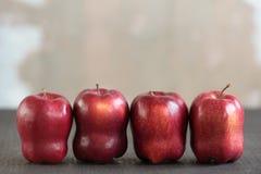 在难看的东西背景的四个红色苹果 库存图片