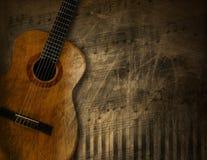 在难看的东西背景的声学吉他 库存照片