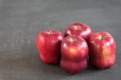 在难看的东西背景的红色苹果 免版税库存图片