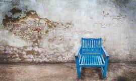 在难看的东西背景的蓝色木椅子 库存图片