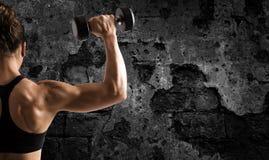在难看的东西背景的运动妇女训练二头肌 图库摄影