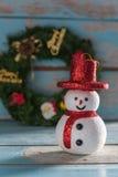 在难看的东西蓝色木后面和礼物装饰的圣诞节雪人 库存图片