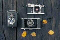 在难看的东西黑暗的木背景的老影片照相机 免版税库存图片