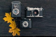 在难看的东西黑暗的木背景的老影片照相机 免版税图库摄影