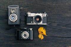 在难看的东西黑暗的木背景的老影片照相机 免版税库存照片