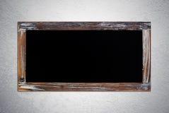 在难看的东西水泥墙壁上的空白的葡萄酒粉笔板 免版税库存图片