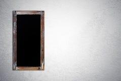 在难看的东西水泥墙壁上的空白的葡萄酒粉笔板 免版税图库摄影