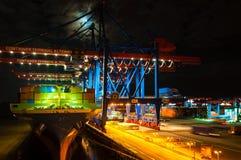 在集装箱码头Altenwerder的大集装箱船在汉堡在晚上 免版税库存照片