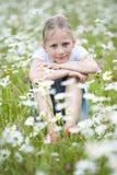 在雏菊之间的草甸安装的女孩 免版税库存照片