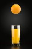 在雕琢平面的一块透明玻璃的橙色和橙汁 库存照片
