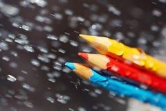 在雨下的三支颜色铅笔 免版税库存图片