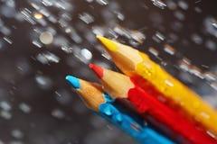 在雨下的三支颜色铅笔 免版税库存照片
