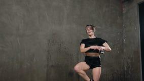 在雨下的当代舞蹈 黑体衣服的湿女孩舞蹈家在阶段做在她自己附近的自转下 股票视频