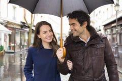 在雨下的英俊的夫妇在街道上 免版税库存照片