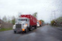 在雨下落的被弄脏的半在路的卡车护卫舰和车灯 免版税库存图片