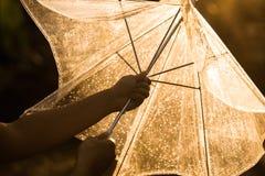 在雨中的妇女手剪影打开一把伞 库存照片