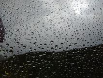 在雨以后浇灌在玻璃的下落 被弄脏的背景 库存照片