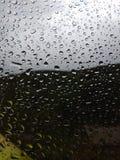在雨以后浇灌在玻璃的下落 被弄脏的背景 免版税库存照片